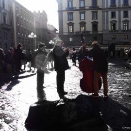 Musicisti in controluce sotto la colonna dell'Abbondanza in piazza della Repubblica.